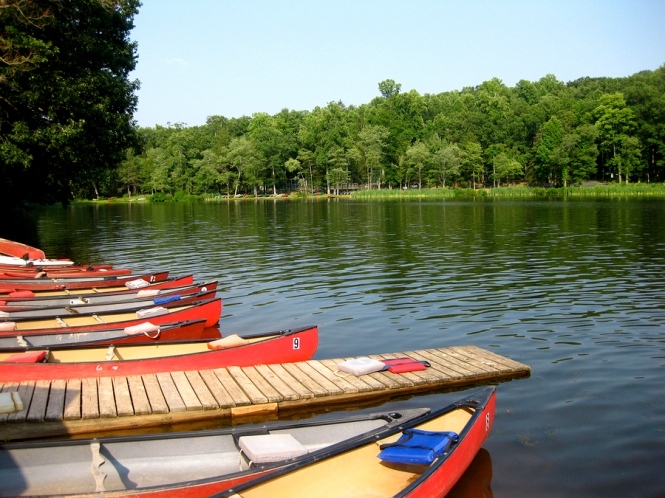 Colorful canoes docked at Mt. Gretna lake on beautiful spring day, tree view across lake