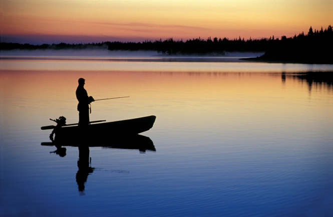 Man standing on john boat holding fishing pole at dusk, boat in center of lake with a treeline in the distance