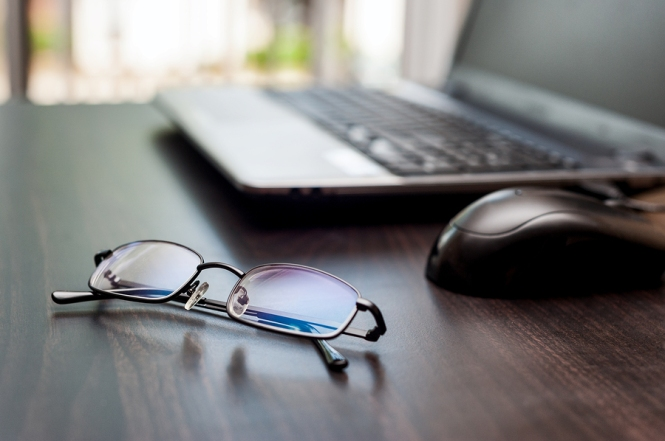 Glasses on a wooden table with open laptop and mouse in the background