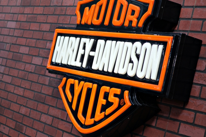 Harley Davidson logo is displayed on a brick  wall