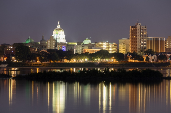 The Harrisburg State capital skyline in Pennsylvania as seen from across the river at night with lights reflected on river surface