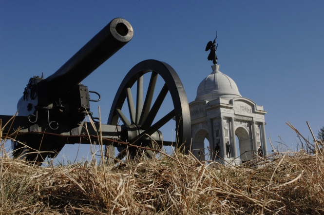 Close up of Civil War cannon on Gettysburg battlefield with the Pennsylvania monument in the background
